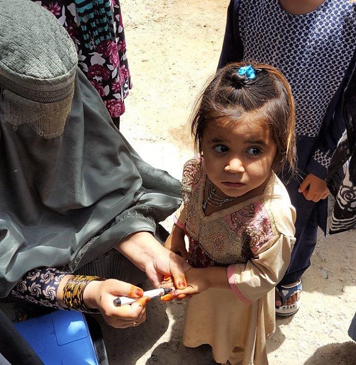 Девочку вакцинируют от полиомиелита в Кандагаре